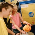 A boy and girl standing next to a blue and beige round table that has a small basket ball on top. In the background are yellow and blue information panels.
