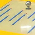 A brushed metal knob with pictures of muliple blue pencils.