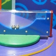 A rectangular blue and clear perspex shape sitting on edge that has two silver balls inside.