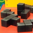 A group of small black cubes joined together in different shapes, sitting on an orange flat surface.