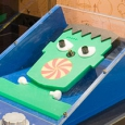 A green cut out face sits behind perspex glass in a blue box.