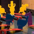 On a dark grey table top sits three rows of red levers with yellow, blue and purple cut out animals shapes.