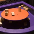 A large purple tray containing wooden building blocks, has a raised orange round platform in the centre of it.
