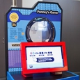 A blue, black and red exhibiti with a round port hole at the top and a red monitor in front.