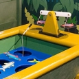 A yellow and blue tub with cut out fish and small fishing poles sits in front of a fake stone wall and jungle scene.