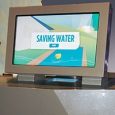 A beige coloured exhibit table with matching monitor on top. On the screen is the title 'Saving Water'.