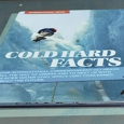 A blue and white opened book with the title 'Cold Hard Facts' displayed.