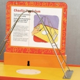 An orange and yellow exhibit table with matching information panel at the back and on the top is a steel arch with a string and black weight hanging down from the apex of the arch.