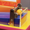 A red and yellow exhibit table, with an orange and white information panel on top. On the table top sits a purple long wedge contained in clear perspex and has a yellow ball at the high end contained by a steel gate.