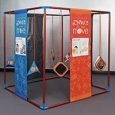 A large red and blue cube frame that has orange and blue information panels hanging from top to bottom. Inbetween these panels are blue and orange trianguular and square objects.