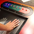 a red display control board, with a screen where you place your hands on, and blue, green and red controls to the top.