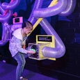 A young girl placing a green scarf in a perspex box that is connect to a series of large air tubes mounted on a purple/blue wall.