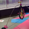 A wheel sits on a cable tightrope, with two masses extending from the wheel so they hang below the cable tightrope