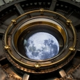 A digital image of the moon sits within a round brass feature.