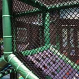 A children's play gym made of black plastic netting, green padded framework and a purple cargo net.