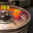 water flowing out of stainless steel tubes onto a perspex dome and into a doughnut shaped basin. There are coloured toys in the basin.