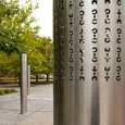 Three stainless steel vertical poles about 2 metres in height are spaced apart and embedded into a concrete and paved garden area. On each of the poles are laser cut out cryptographic symbols.