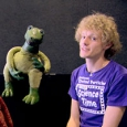 A man with a purple t-shirt is sitting next to a green dinosaur puppet.
