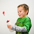 An excited small boy with a green t-shirt, squeezing a plastic bottle and a red feather coming out of the top.