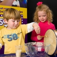 A small boy and girl playing with a drum and mixing bowl.