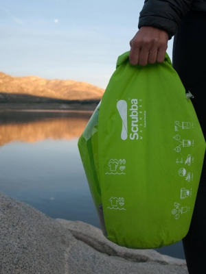 A traveller holds Scrubba Wash Bag in the wilderness