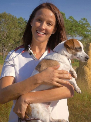 Dr Susanne Samuelsson stands in the Australian outback holding a dog.