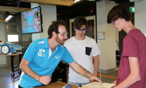 A Questacon staff member helps two teenage boys work on a model bridge.