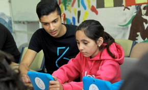 Taj Pabari, founder of Fiftysix Creations, works with a student