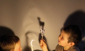 Two young boys sitting in a darkened room with a light shining between them onto a wall behind. They are holding up a cut out of a moon and cow on sticks, which both cast shadows onto the wall.