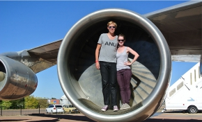 A man and woman standing beside one another and both wearing dark sunglasses. They are standing in the engine turbine of a jet aircraft.