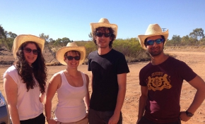Two men and two women all wearing white hats and sunglasses standing in remote Australia.