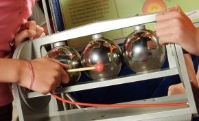 A boy and girl standing in front of a green and blue vertical information panel have their hands on a grey framed exhibit, which has 3 chrome spheres. The girl has a small mallet, and is hitting the centre sphere.