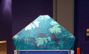 A blue, green and grey exhibit stand with a large piece of timber at the front with slots cut into it.