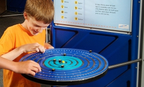 A boy is playing with black markers on a series of blue rings that represent the solar system. In the background is a blue information panel.