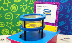 A red and blue exhibit table with a yellow, white and purple information panel on top, sits in front of two green and blue walls. On the table sits a blue, black and clear perspex cylinder shpaed aquarium.