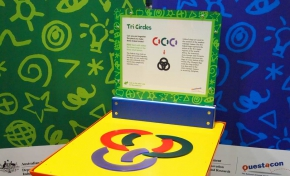 A red and yellow exhibit table, with a blue, green and white information panel on top, sits in front of a green and a blue wall. On the table sits a purple, a red and black circles that have been broken into two pieces each.