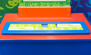 On a blue and orange surface sits a flat green and white word puzzle, set in a blue frame.