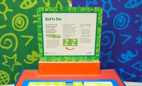 A blue and red exhibit table, with a green, white and orange information panel on top, sits in front of a green and a blue wall.