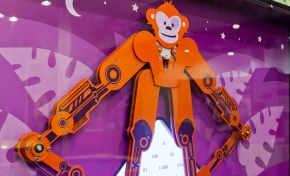 An orange mechanical monkey in front of a purple background.