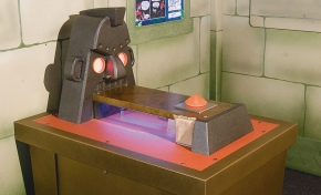 A brown exhibit table with a steel mask with glowing eyes sitting on top, and a rectangular platform coming out of the statue's mouth. In the background is a fake stone wall with a blue, white and green information panel.