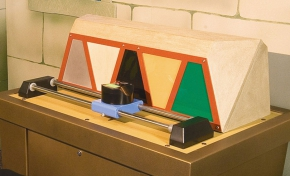 A colourful mosaic sits on a brown table, behind a blue and black camera, that is attached to two steel rails.