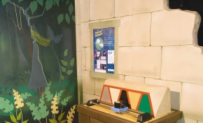 A brown exhbit table with a colourful mosaic on top, that is behind a blue camera that is on steel rails. In the background is a fake stone wall with a green, white and blue information panel, and there is a second wall painted like a jungle.