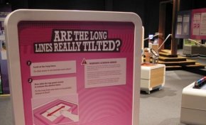 A cream and pink exhibit table and display board with the title 'Are the long lines really titled?'. Two squares with diagonal lines appear on the table top.