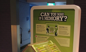 A green and cream coloured exhibit table with the words 'can you make up a memory' on it. on the table top are two boards resting at 90 degrees towards each other.
