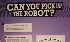 A cream and purple coloured exhibit table with headboard that has 'Can you pick up the robot?' written upon it, followed by instructions. There is a small gold robot in the centre of a red ring on the top of the table.