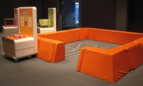 A cream and orange exhibit table stands in front of orange knee high padded fences that re sitting on brown-grey carpet.