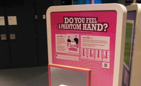 A cream and pink exhibit table and back board that has a vertical mirror on the table and the words 'do you feel a phantom hand?' on the backboard.