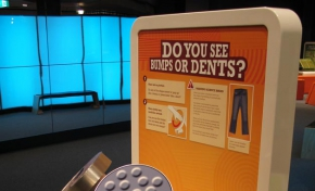 A cream, orange and yellow exhibit table and backboard, wit the words 'Do you see bumps or dents?'. On the table sits two round displays that have grey bumps and dents on the surface.