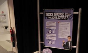 A cream and purple exhibit table with back board that has the text 'Does swapping stereo fool your eyes?' displayed. A clear plastic head sits on a purple flat disc along with black headphones on the table top.