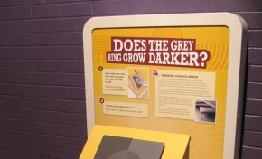 A cream and yellow exhibit table and headboard with the title 'Does the grey ring grow darker?'. A grey square and circle sit on the table top at 45 degrees.